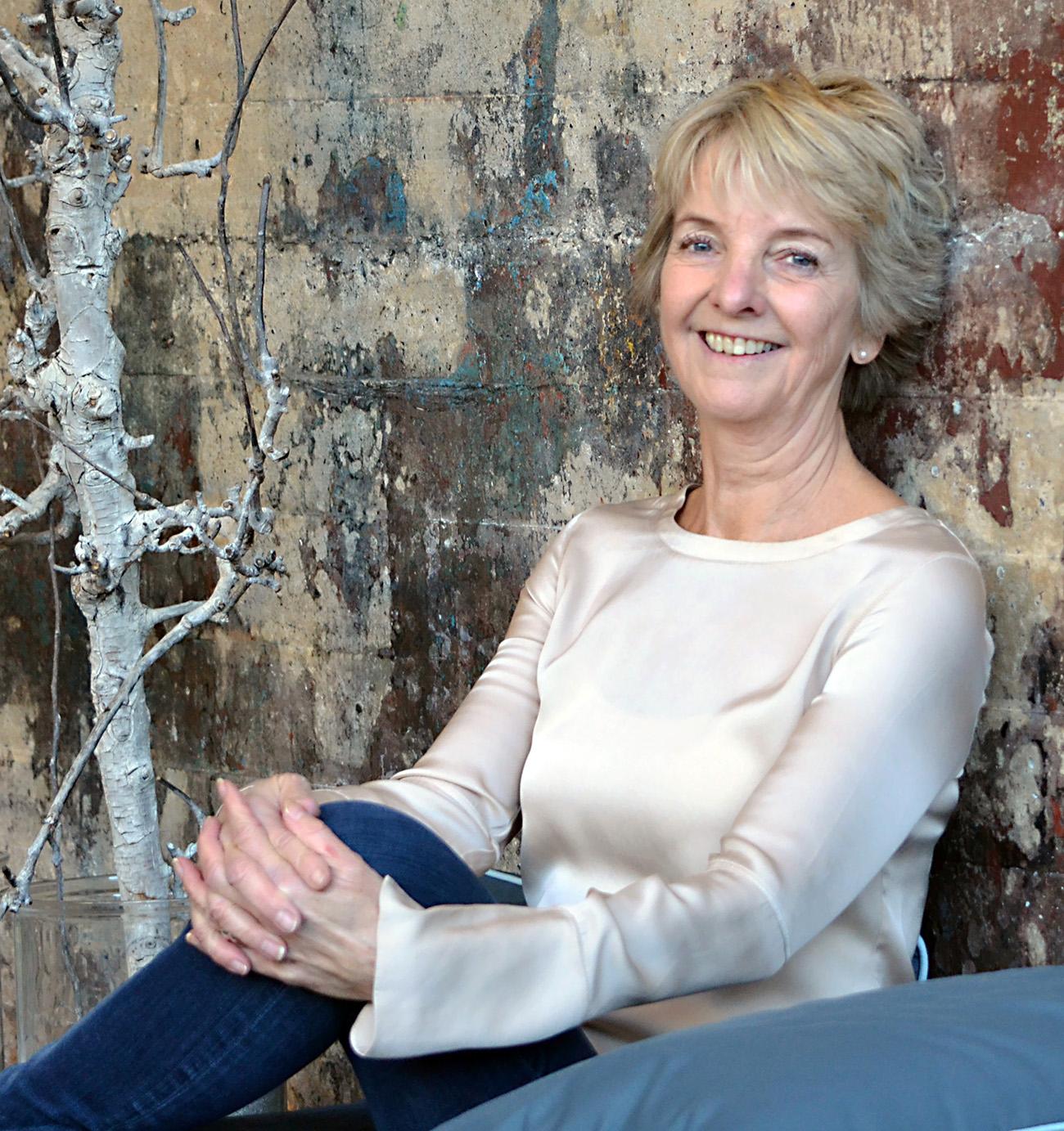Eva Holten iført hvid silkebluse læner sig op ad rustikmalet væg