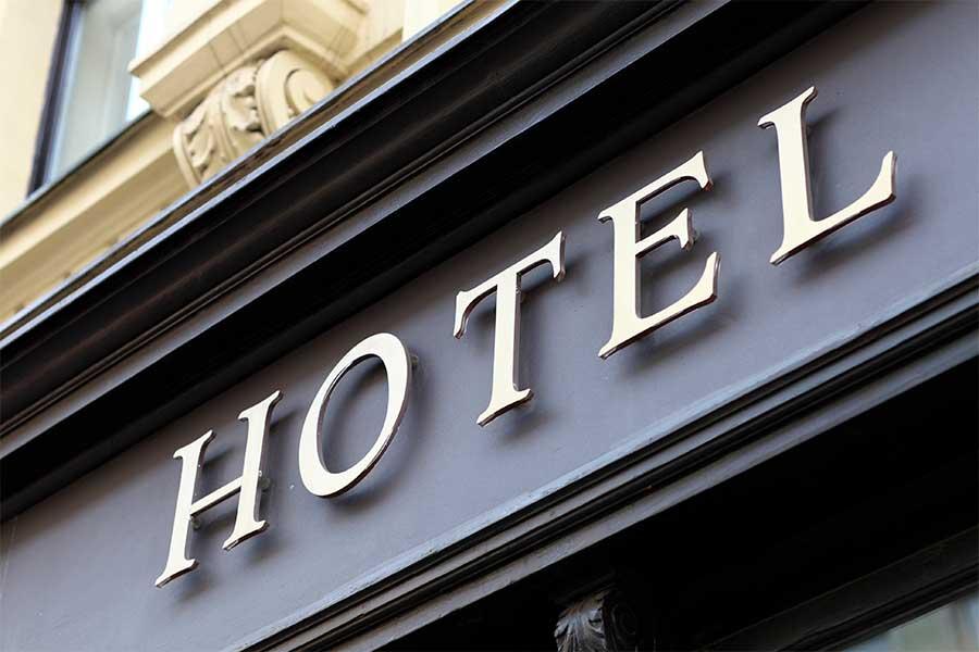 HOTEL skrevet med guldbogstaver ovenover indgangsparti til hotel