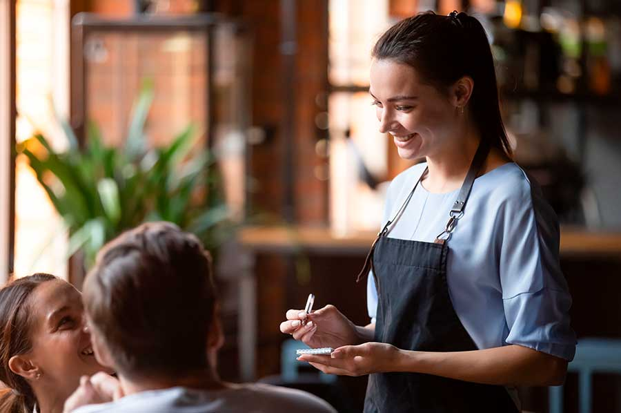 smilende servitrice tager imod gæsters bestilling