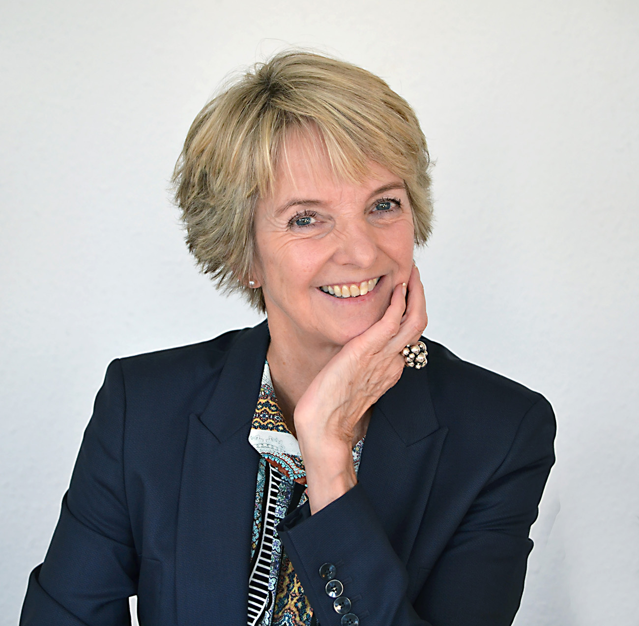 Eva Holten smiler med ansigtet hvilende i den ene hånd