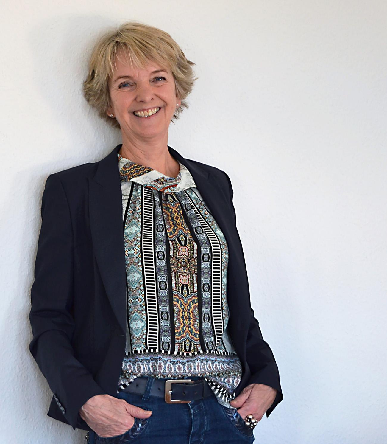 Eva Holten læner sig op af væggen og smiler iført business-jakke